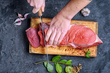 This is a top down image of a person cutting meat with a sharp knife.