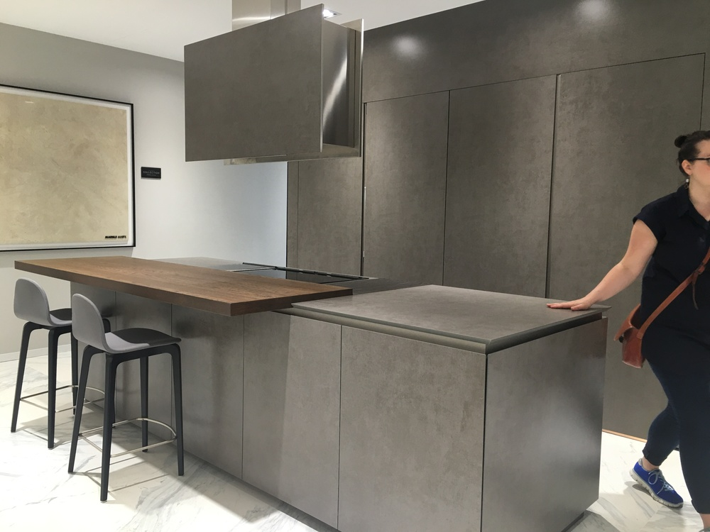 A minimalist kitchen, with pocket door detailing and simple breakfast bar
