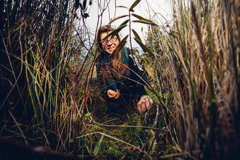 An Alderleaf student hunts for bog cranberries amongst dense grasses.