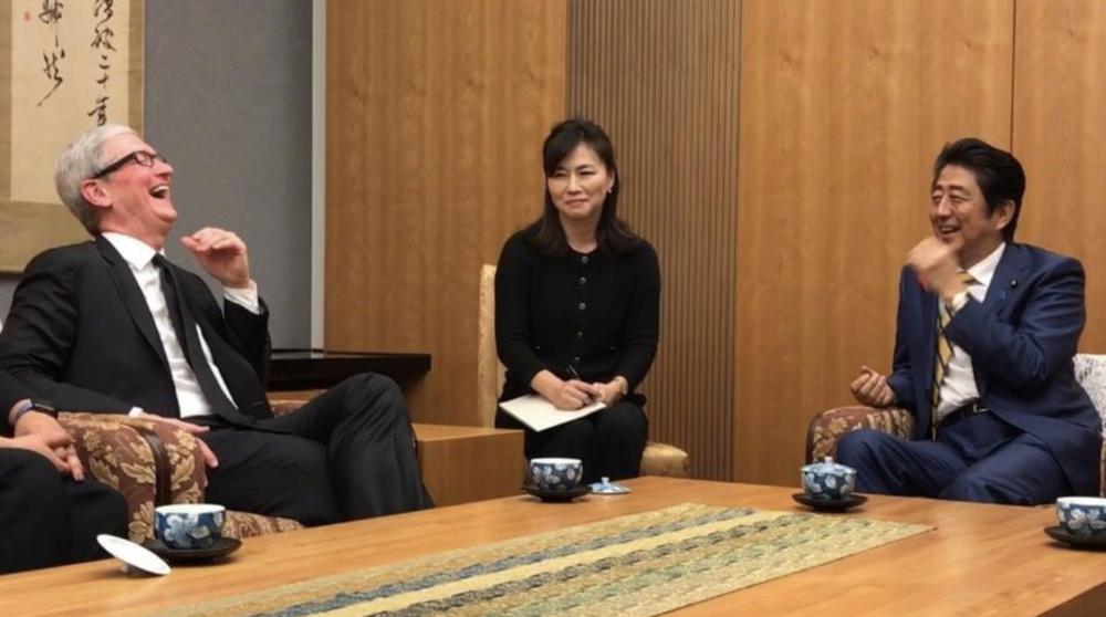 Apple CEO Tim Cook (left), translator, Japanese Prime Minister Shinzo Abe (right).