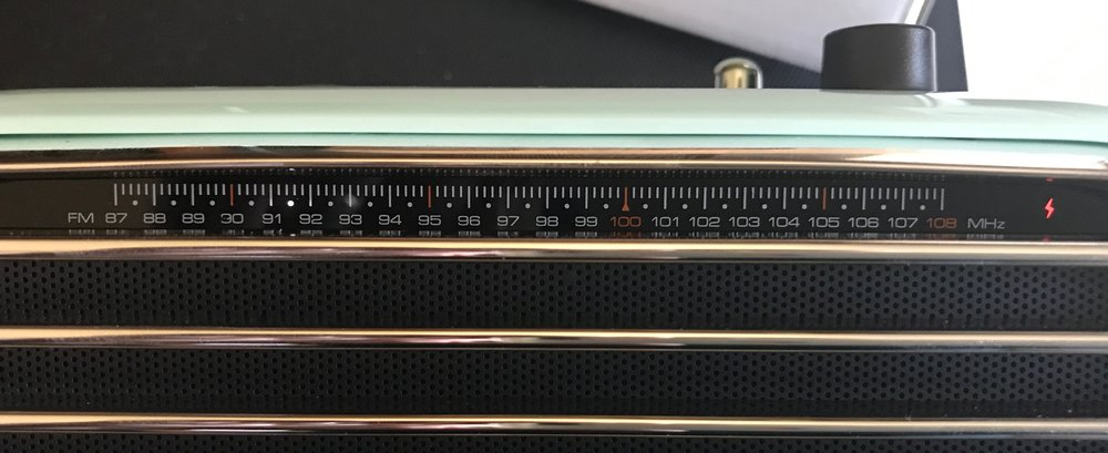 "The FM tuner, with white LED showing frequency and red ""lightning bolt"" indicating signal."