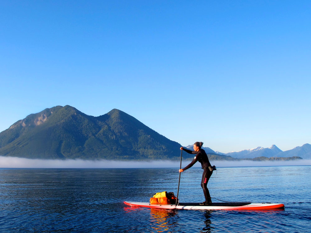 A lady stand up paddle boarding in Tofino, BC.