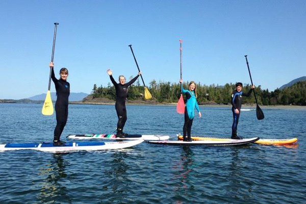 Family on a stand up paddle board tour in Tofino, BC.