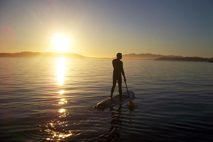 A man stand up paddle boarding in Tofino, BC at Sunset.