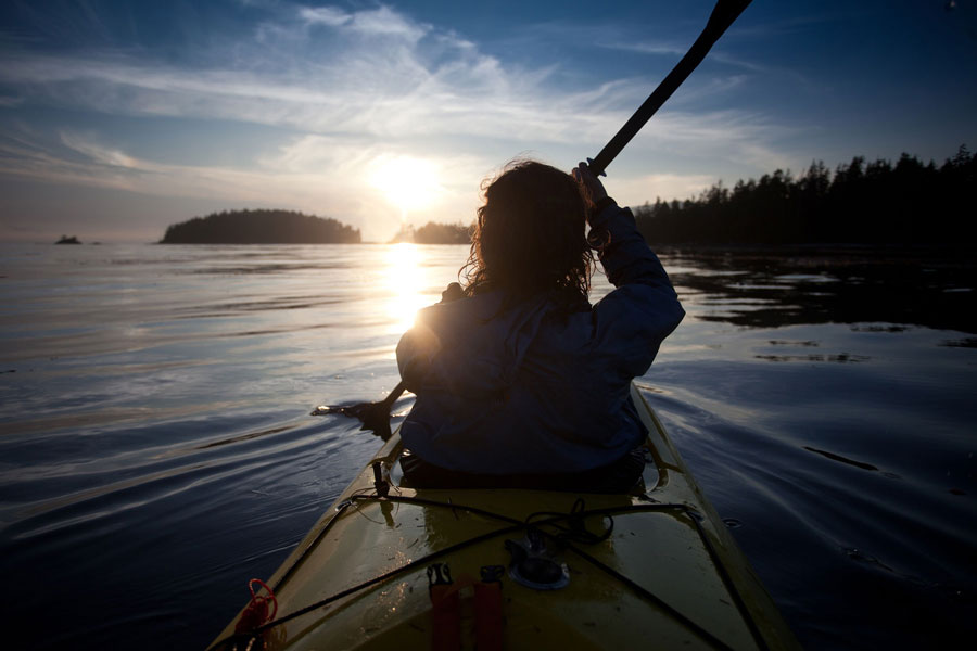Woman kayaking in Clayoquot Sound with sunset in background.