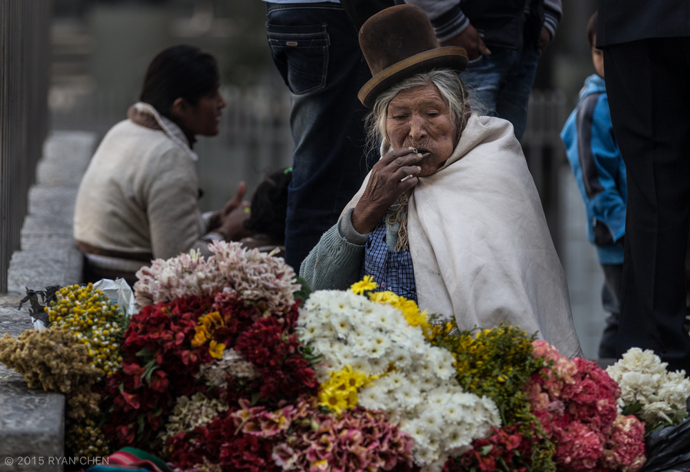 6111235d5a159 Women in Bolivia typically carry on the cultural traditions. This flower  vendor wears her bowler