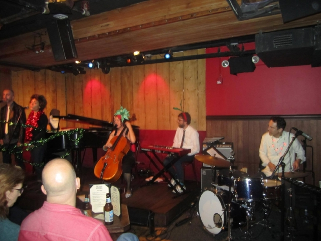 L to R: Adam Enright & Madison McFerrin, backup vocals, Aya Kato as RASTA SANTA, Erin Hall w/Holiday Hat by BRIJ DESIGN, Gabe Shuford on Keys, John Bollinger on drums (NOT PICTURED-- Lars Jacobsen on Tenor Saxophone. Special Thanks to Will running sound! ! ! #RockwoodMusicHall #cello #comedy #holiday