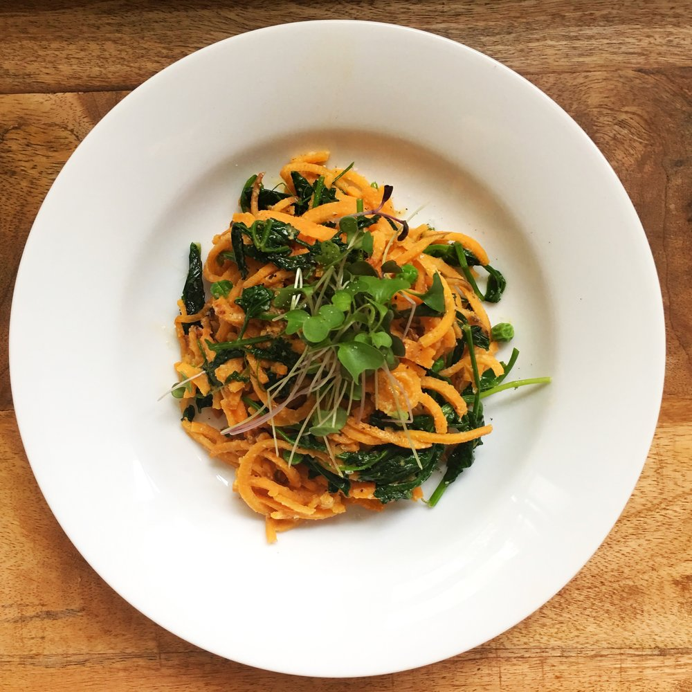 Sauteed sweet potato noodles with wilted pea shoots, roasted garlic cashew cream and kale microgreens. Photo: Mary Ackley (@littlewildthingsfarm)