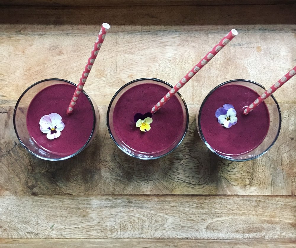 Kale microgreen and dark cherry smoothies with edible violas. Photo: Mary Ackley (@littlewildthingsfarm)