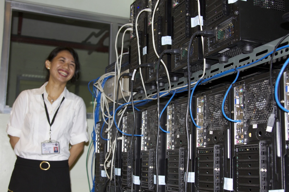 UP-Diliman PhD student Belay Montes with the cluster of T3 servers powering the CloudTop system