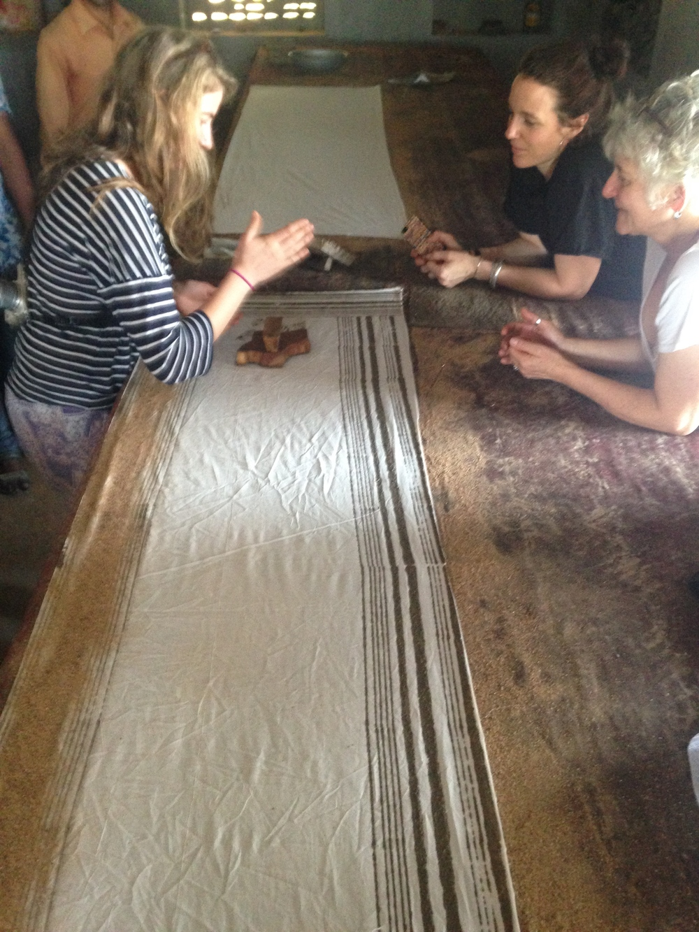 Fellow textile desperadoes trying their hand at mud resist woodblock printing. The secret: a very gentle dab of the woodblock into the pad of bud and a swift  chop  with the side of the hand to apply the mud to fabric.