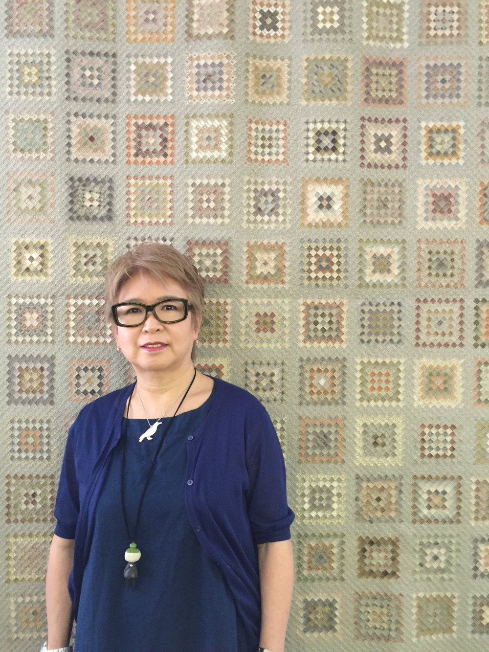 "Ms. Yoko Saito posing in front of her ""Around the World"" quilt, over 20,000 pcs of 1 cm squares all pieced by hand. Photo taken at Quilt Party, Ms. Saito's quilt shop and school in Ichikawa City in Chiba, Japan in 2016."