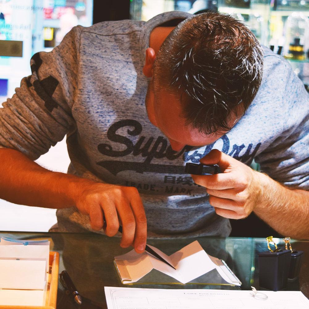 Customer Examining a Row of Diamonds