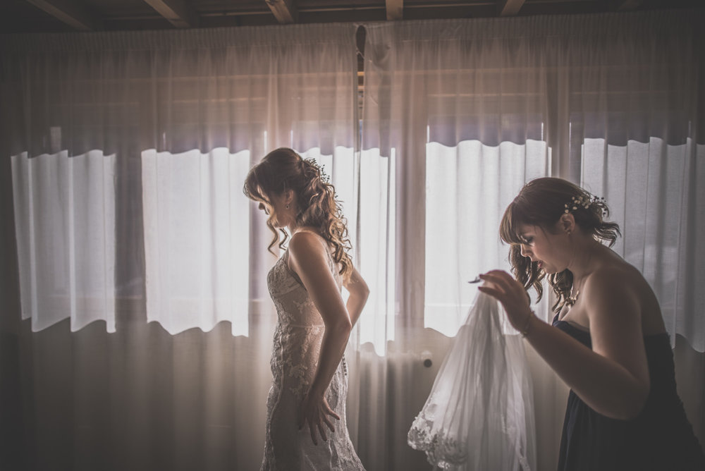 bridesmaid helping the bride to get ready