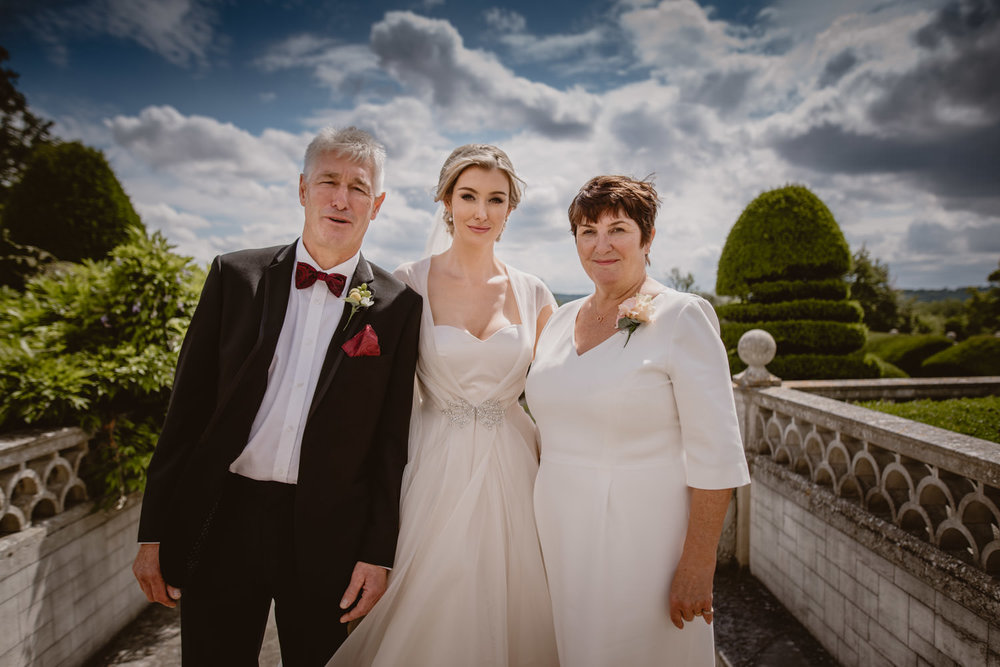 Group photo of the bride, her father and her mother during the wedding day at Danesfield Hotel Wedding Venue in Marlow-On-Thames, Buckinghamshire