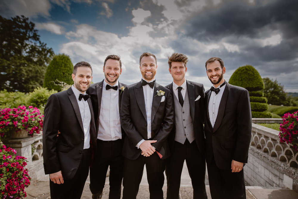 Group Photo of the Groom, Ushers and Groomsmen at the gardens of Danesfield Hotel & Spa next to  the Thames