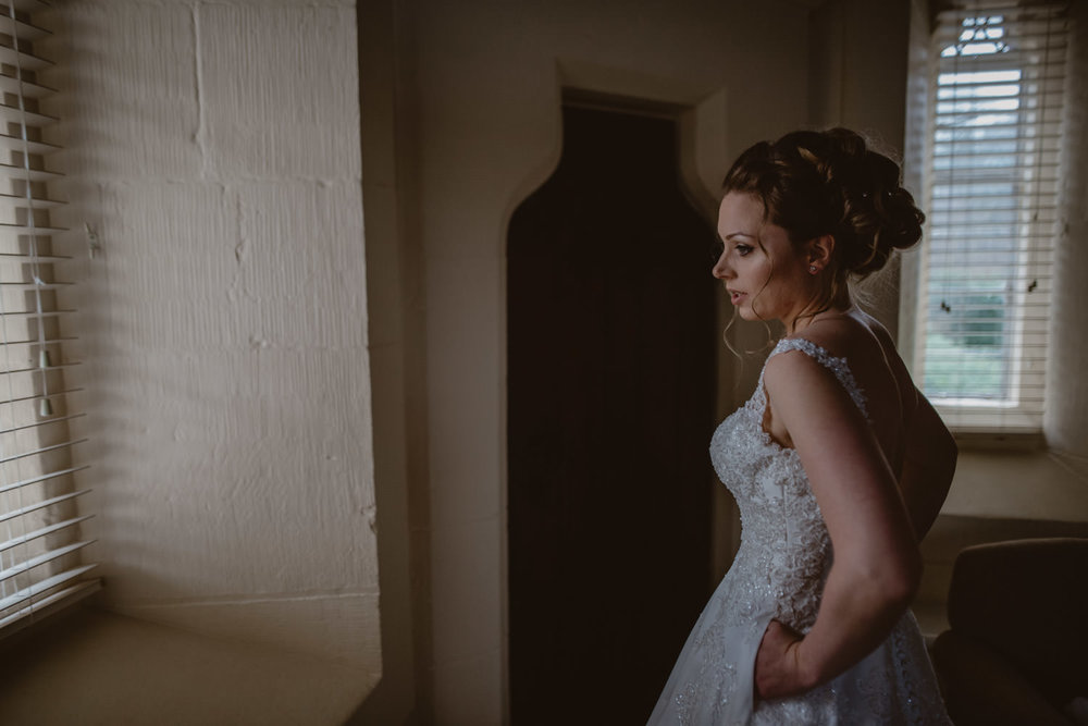 Bride wearing the wedding dress for the first time before the ceremony at Peckforton Castle