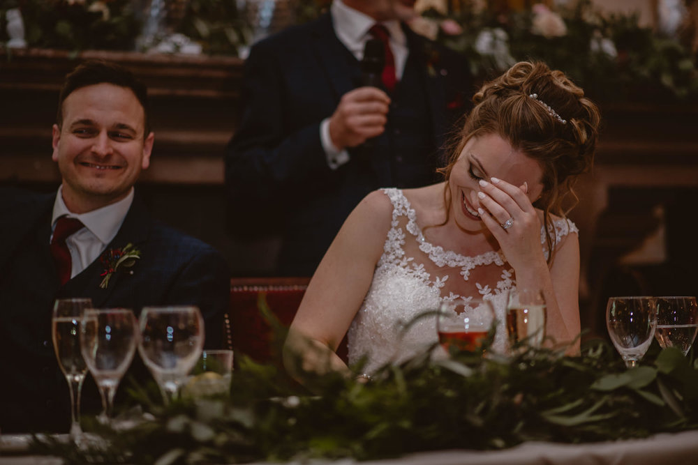 Bride laughing during the speeches on her wedding day at Peckforton Castle