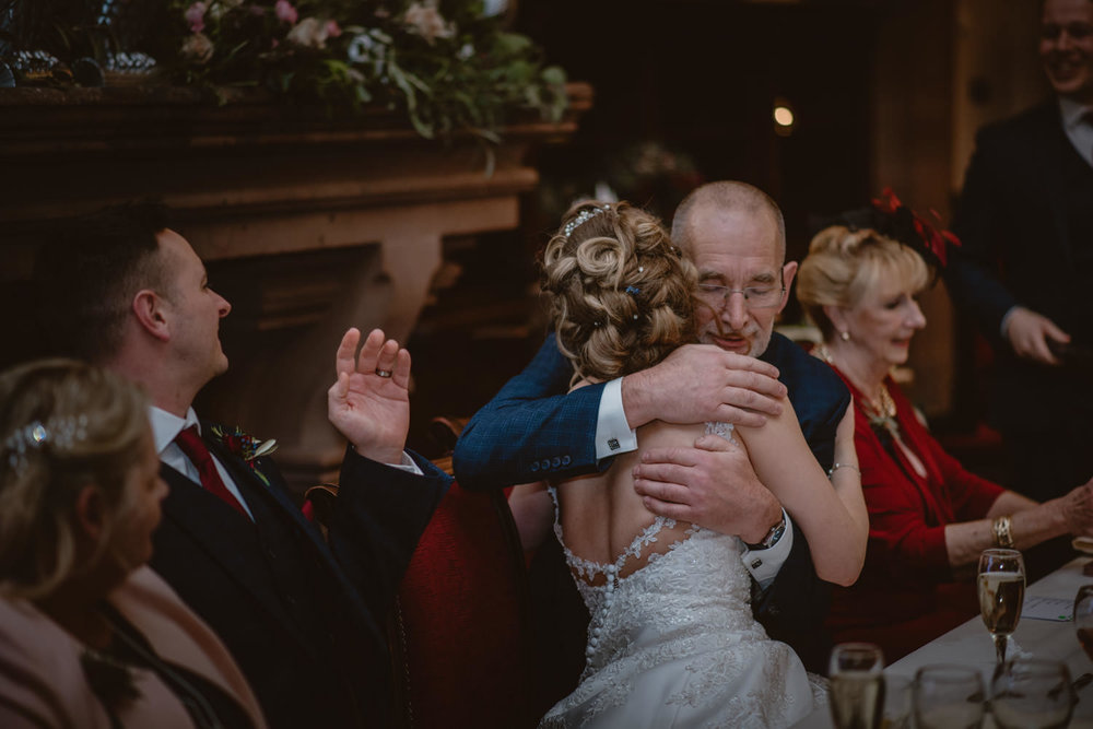 Bride hugging her father after the speech on her wedding day at Peckforton Castle