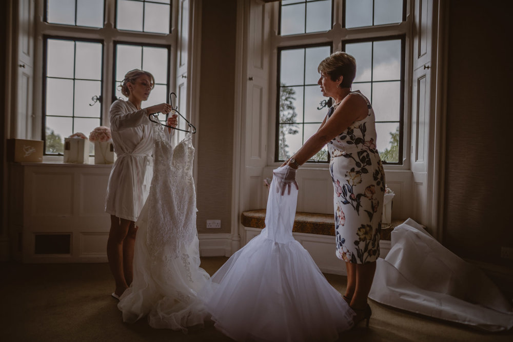 Mother of the bride helping her daughter to get ready for the wedding day at the Elvetham Hotel in Hampshire