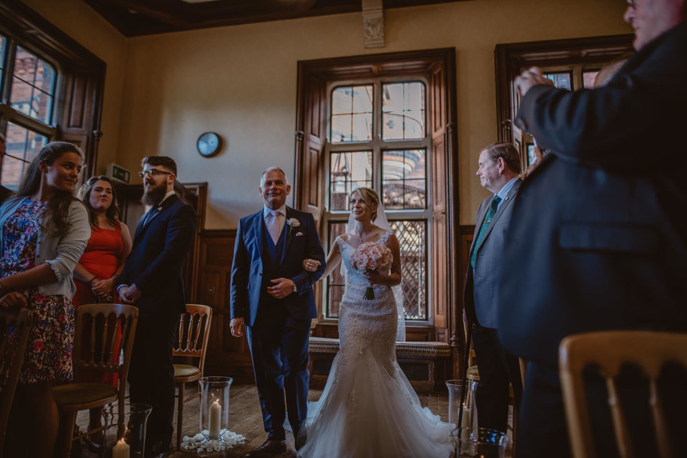 Bride walking the aisle in The Elvetham Hotel Oak Room in Hampshire