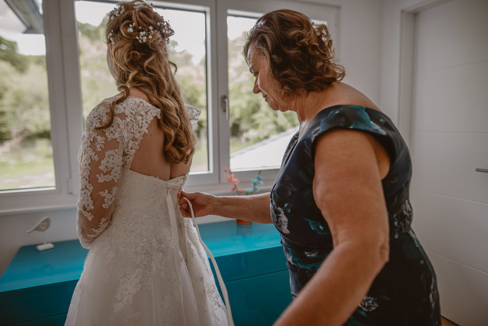 mother of the bride helping her daughter with the wedding dress