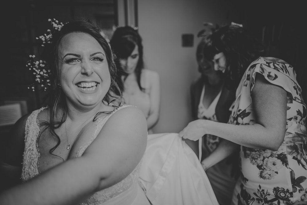 Friends helping the Bride with the dress
