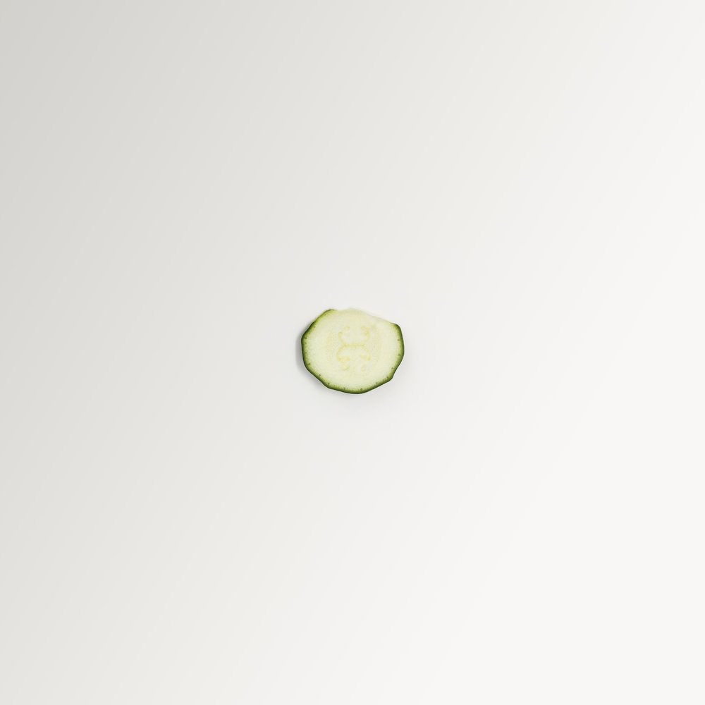 A simple, minimalist, contemporary, fine art photograph of a slice of cucumber