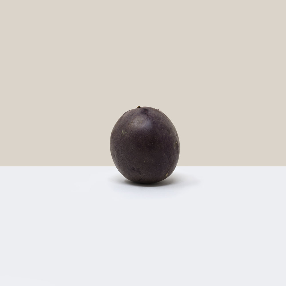 A simple, minimalist, contemporary, fine art photograph of a passionfruit