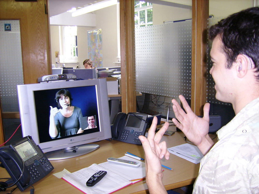 Deaf_or_HoH_person_at_his_workplace_using_a_Video_Relay_Service_to_communicate_with_a_hearing_person_via_a_Video_Interpreter_and_sign_language_SVCC_2007_Brigitte_SLI_+_Mark.jpg