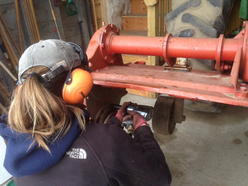 Lise working on our rototiller which will be used next month to flatten beds for seeding in the field.