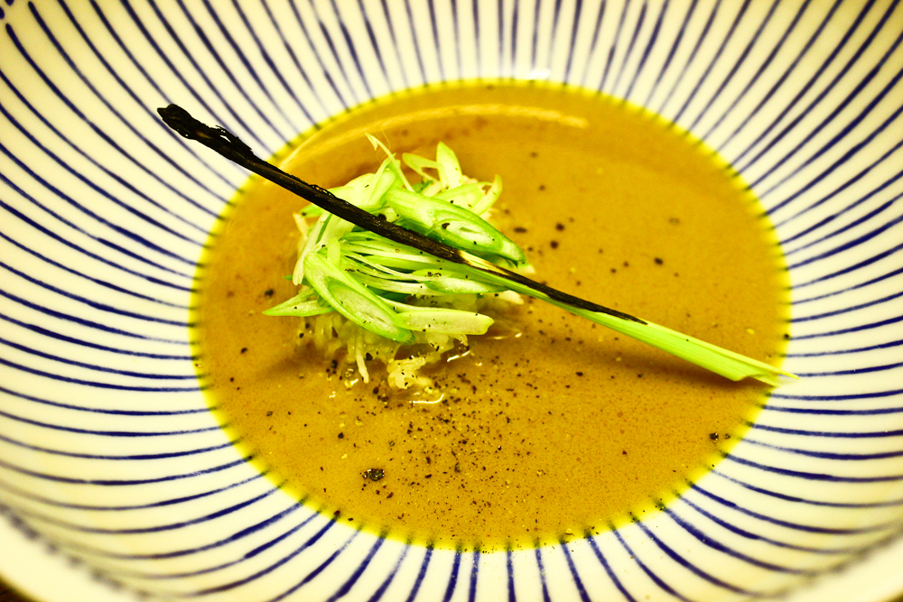 Soup made with smoked and roasted gilthead bream heads, coconut milk, lemongrass and kaffir lime leaves, fresh turmeric root. In the bowl are shredded turnips, fermented in yoghurt whey for ten weeks, spring onions and a charred lemongrass leaf