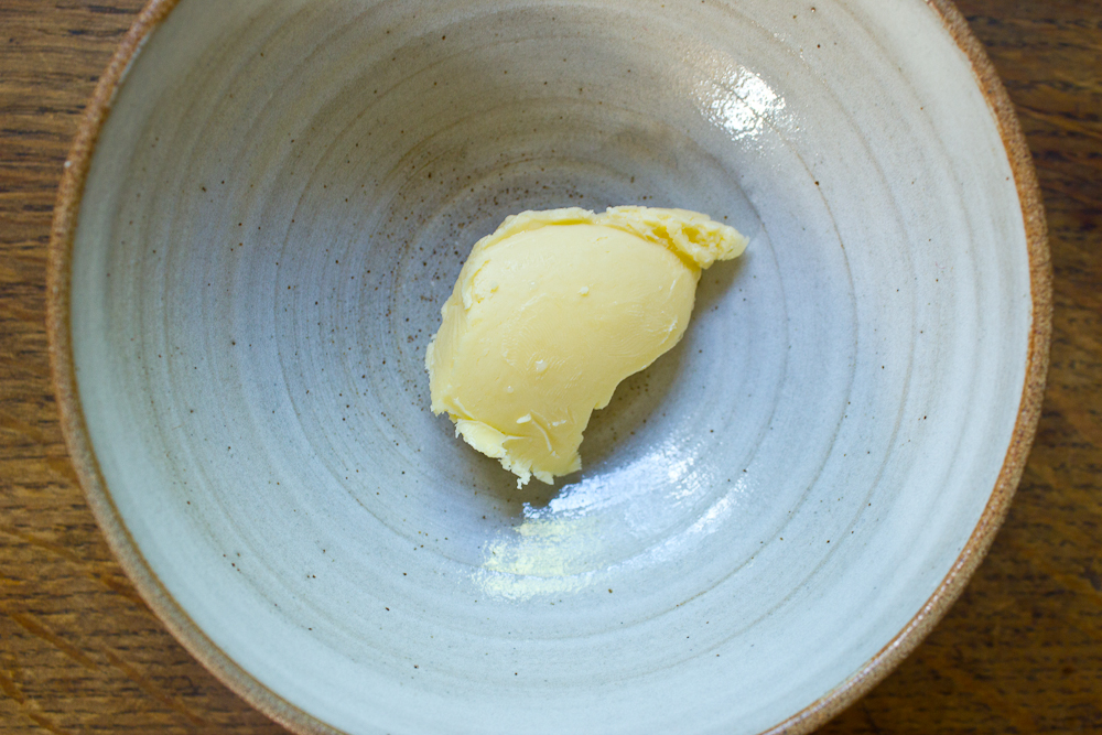 Aged butter From a batch of raw (unpasteurised) double cream from Helsett Farm in Cornwall. I allowed the cream to ferment for 6 days in the fridge at around 3℃, and then at room temperature (20℃) for another 6 days. I whipped it, strained the buttermilk, and served the first serving. Then I used the butter at various intervals over the next four days, before wrapping it and storing it the fridge for some long ageing. Two weeks have passed, and the butter has a deep savoury smell and taste. The milk was given by Ayreshire cows to an automatic 'self-milking' machine on May 16th, 29 days ago. Eighty litres of milk were skimmed to produce six litres of double cream. I don't know the fat content, but it was definitely not low. I have stopped serving the butter to the public, and will continue to monitor and eat it until it tells me not to.   I recently bought the bowl in the picture from a local potter and gardener called Jan Pateman, who has a stall in Herne Hill Farmer's Market.
