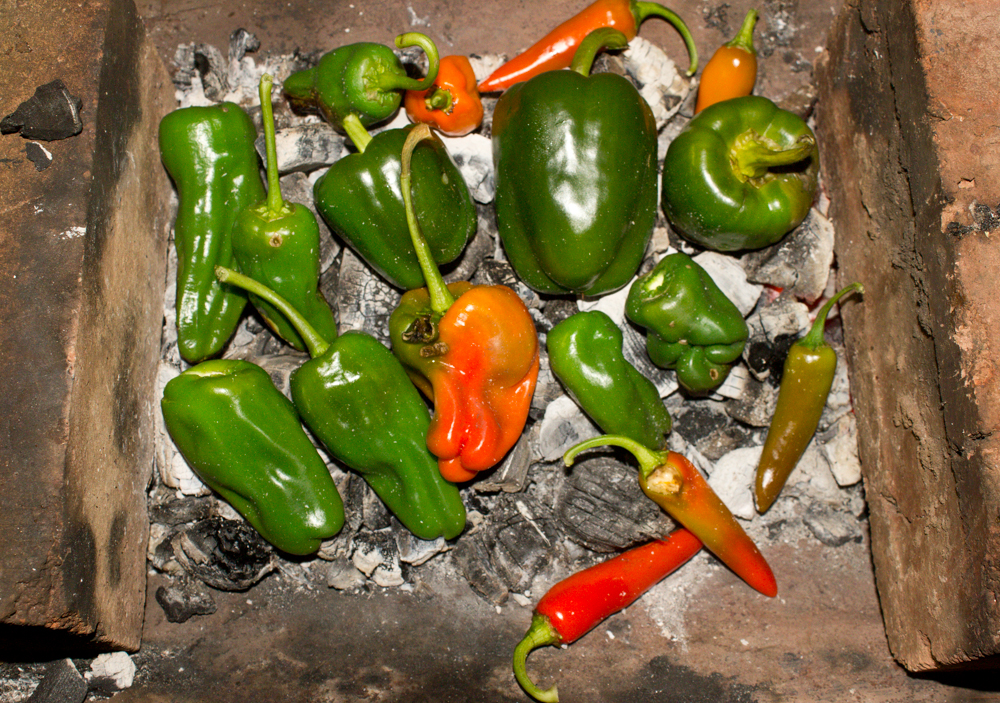 Charring peppers in embers