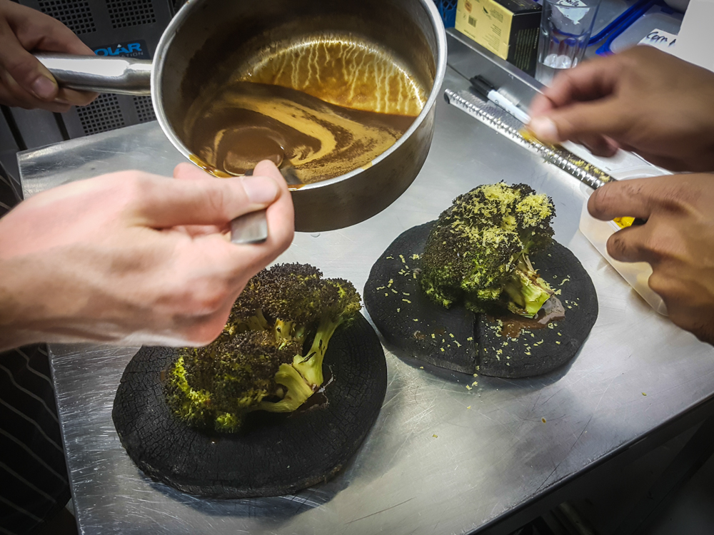 Shaving cured egg yolks over roast broccoli