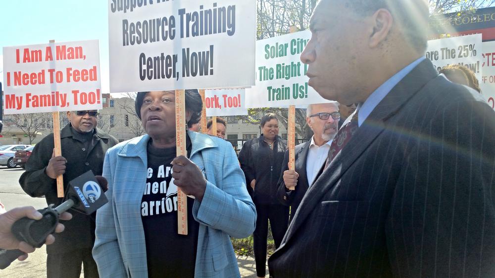 Legislator Grant (center) and Charley H. Fisher (right) speak to news media atprotest rallyand press conference.