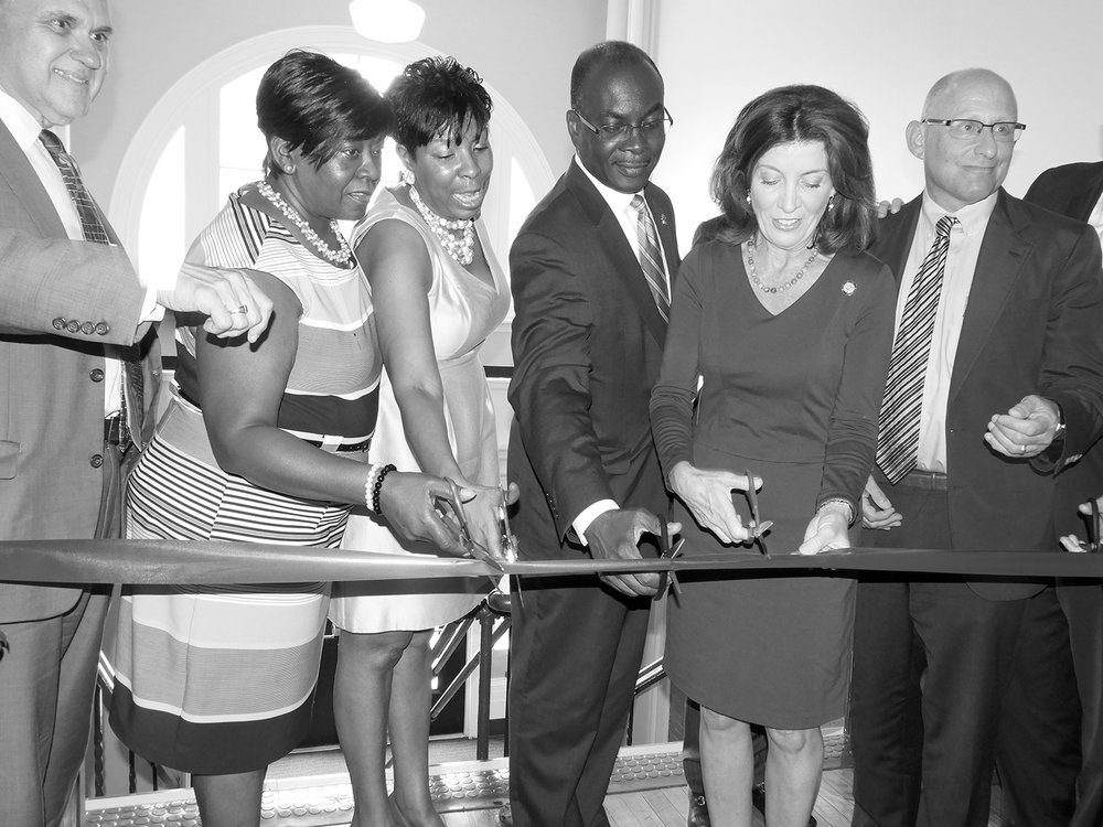 RIBBON CUTTING: Rhonda Ricks, fourthfrom left joins Mayor Brown, Assemblywoman Peoples-Stokes and others in last Thursday's ribbon cutting.
