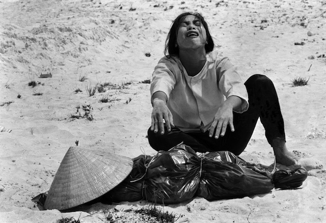 A woman mourns over the body of her husband after identifying him by his teeth, and covering his head with her conical hat. The man's body was found with forty-seven others in a mass grave near Hue, April 11, 1969. The victims were believed killed during the insurgent occupation of Hue as part of the Tet Offensive. (AP Photo/Horst Faas)