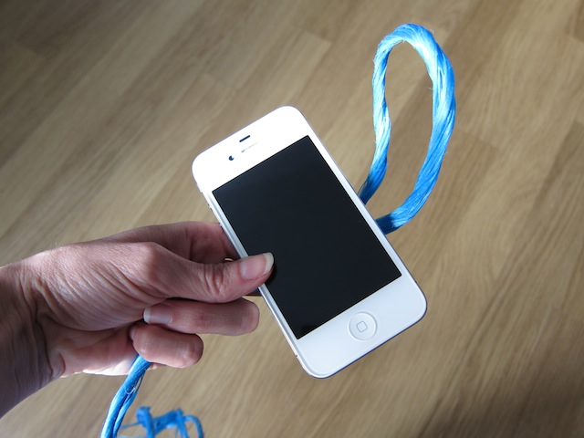 Take a loop of string and secure it around your smartphone in girth hitch