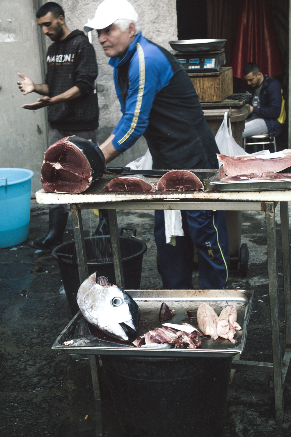 Vendors preparing their fish at La Pescheria, Catania, Sicily