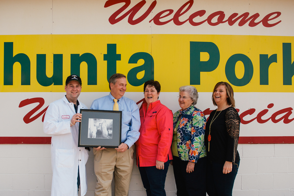 "Bradon, Larry, Rita, Jean, and Lauren pose for a photo with a portrait of Mack ""PigPop"" Pierce holding his largest and most prized 1,105 pound salughtered hog. The Pierce family runs the Nahunta Pork Center and Hog Market, keeping family values and respect at the core of their business."