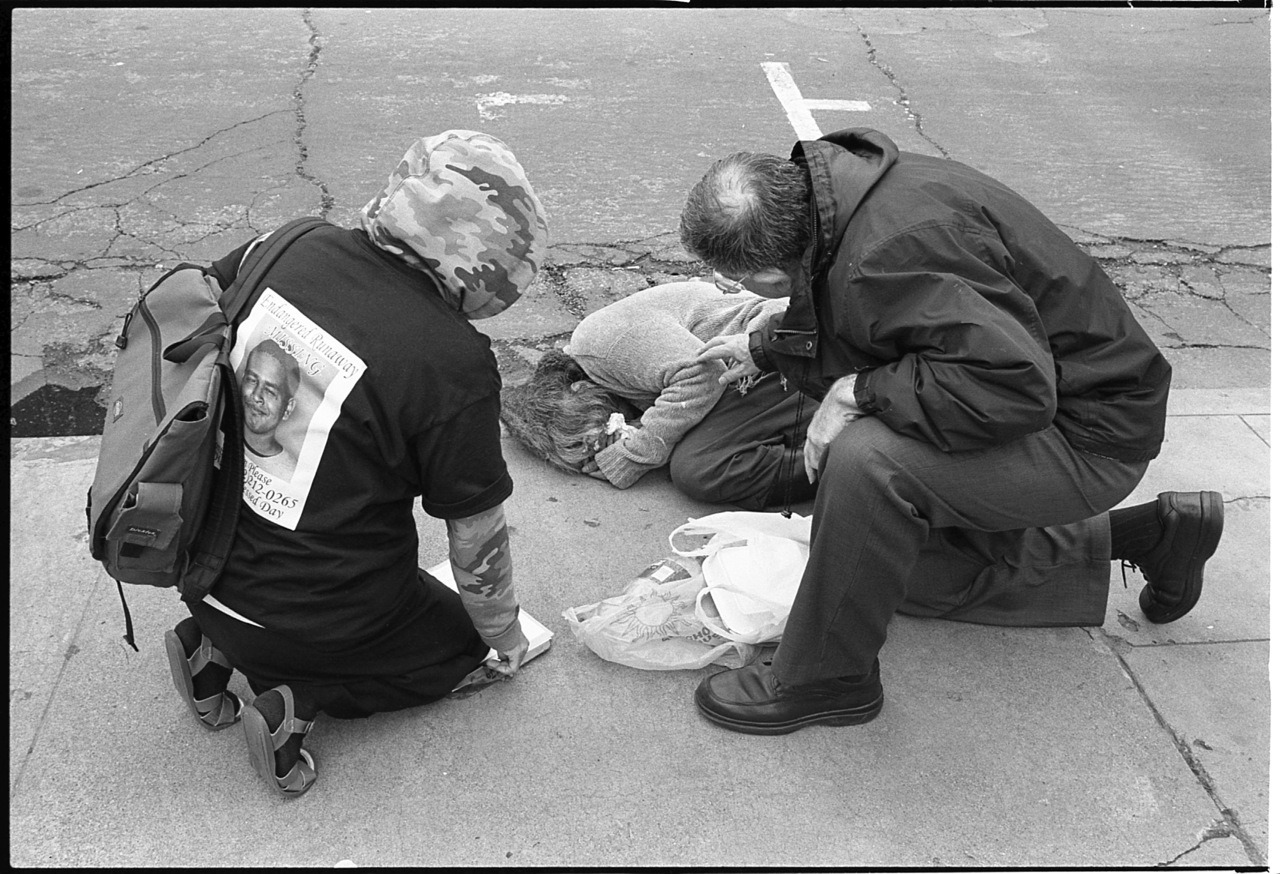 """Tending to a sick woman in front of St. Mary's Church on Washington Street."" Taken by  Brandon Getty  and found via  American Guide ."