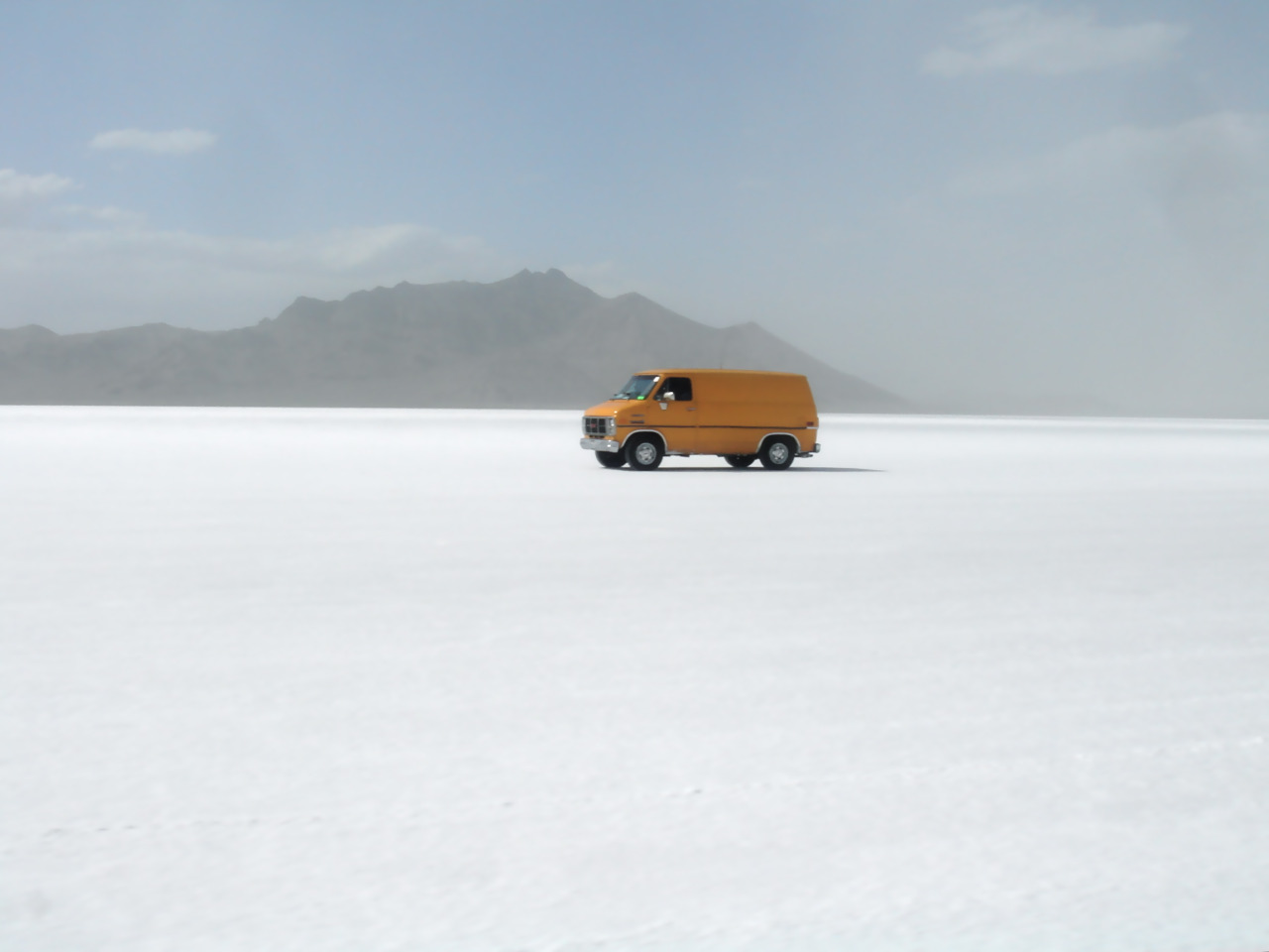 stephanegoin :     Salt lake City / UT     Actually, well west of SLC: this is the Bonneville Salt Flats, a flat white desert of salt crystals west of the Great Salt Lake where most of the world's land speed records have been set. I do not believe that's what this orange GMC van is up to, though.