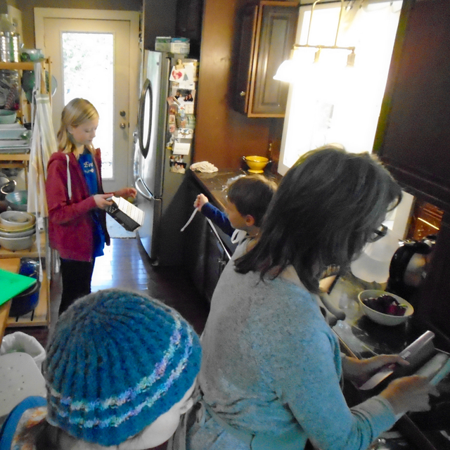 A gaggle of children learn how to sauté chicken in Joyce's kitchen.