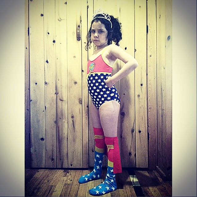 This is what happens when one of Mama's friends falls in love with the girl: a Wonder Woman swimsuit and caped socks.