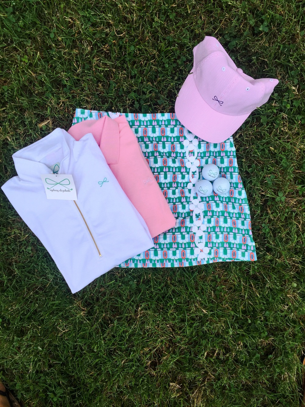 Skylar Popover in white, Lexi Polo in pink, Adelaide Skort, and SE Logo Hat in pink/white