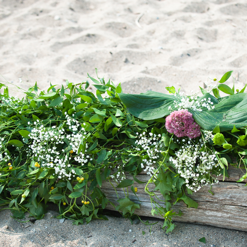Incorporating some driftwood found on the beach into a beautiful floral installation
