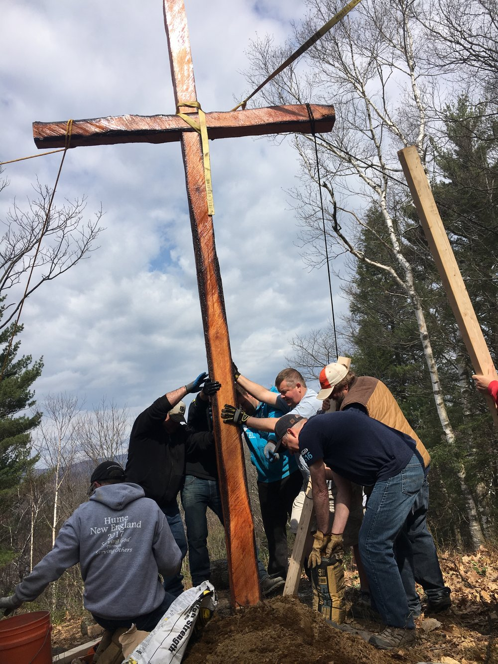 Staff and volunteers working together to place the cross.