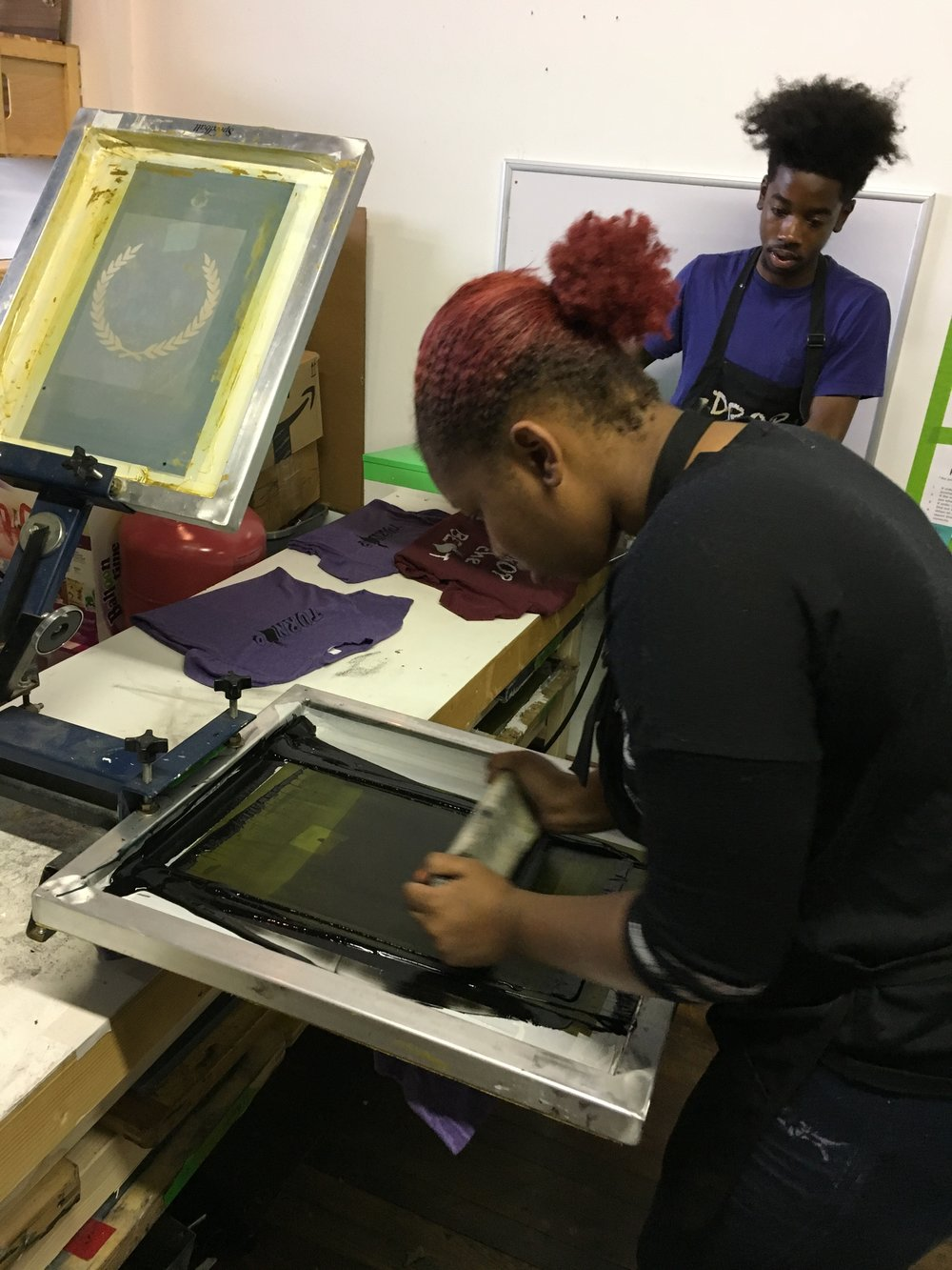 Charles teaching Arianna the ins and outs of screen printing.