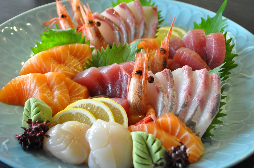 """Their sushi and sashimi platter arrived. Both his hands were required for handling chopsticks, dipping raw fish into soy wasabi trays, and sipping a small cup of green tea. Aspects of his seduction were taking a break."""